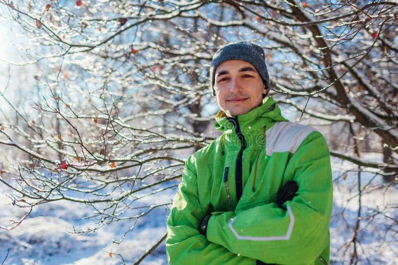 Jonge mens die sportieve kleren in de winter boskerel dragen die camera met gekruiste handen bekijken royalty-vrije stock foto