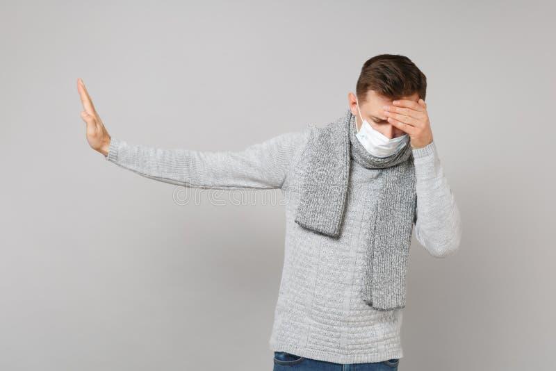 Jonge mens die in steriel gezichtsmasker met verminderd hoofd handen op voorhoofd zetten, die eindegebaar met palm opzij tonen stock foto