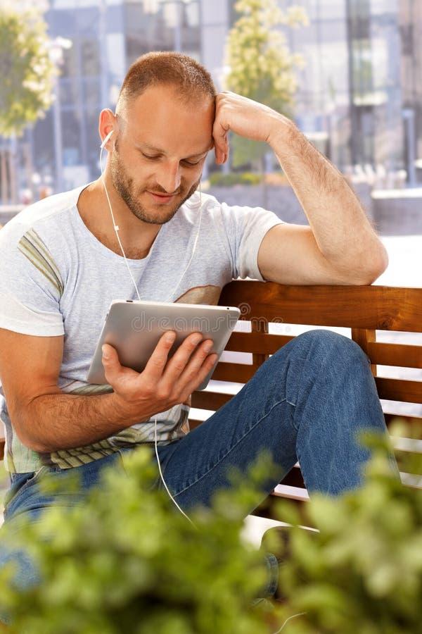 Jonge mens die tablet gebruiken en earbuds royalty-vrije stock foto's