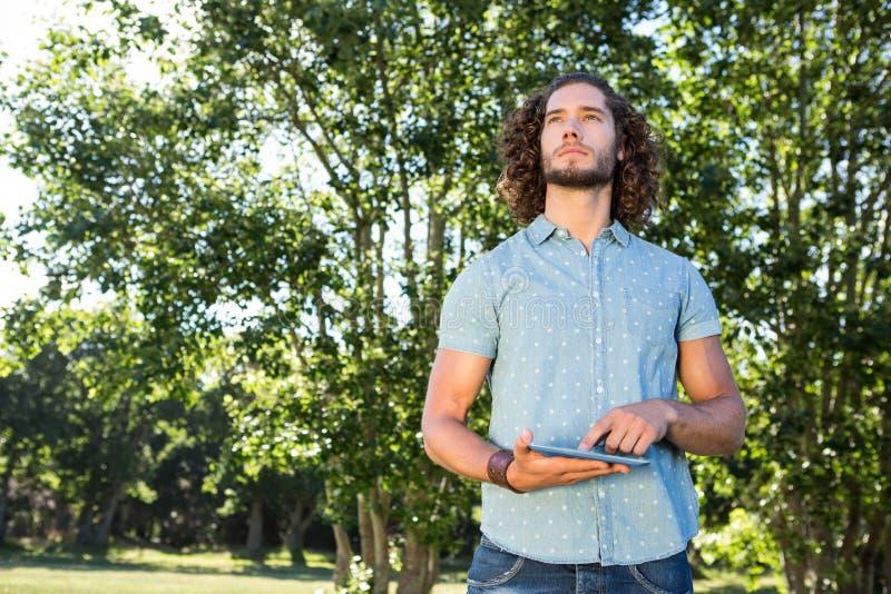 Jonge mens die tablet in het park gebruiken stock afbeelding