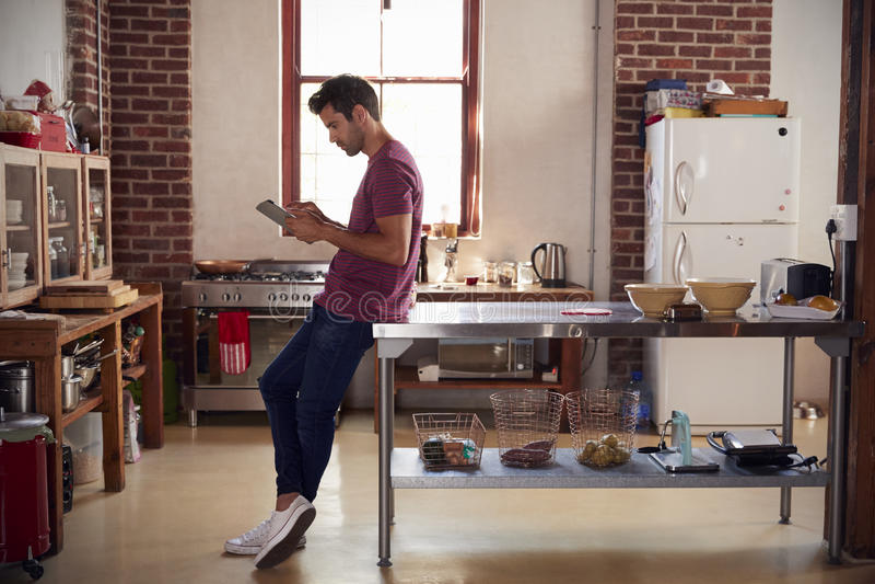 Jonge mens die tabletcomputer in keuken, volledige lengte met behulp van