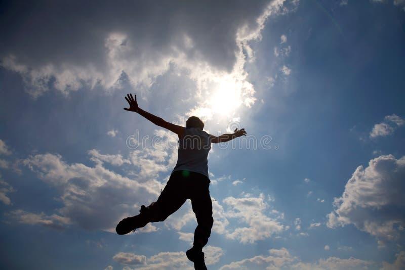 Jonge mens die tegen bewolkte hemel springt royalty-vrije stock afbeelding