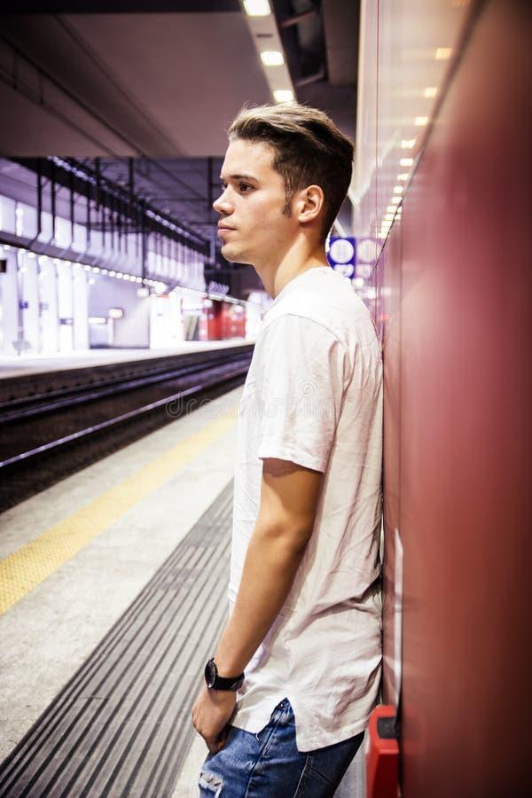 Jonge mens die tegen muur zich aan de gang of metropost bevinden stock afbeelding