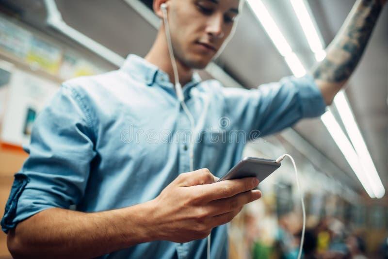 Jonge mens die telefoon in metro, verslaving met behulp van royalty-vrije stock afbeeldingen