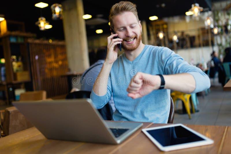 Jonge mens die telefoongesprek in koffiewinkel hebben stock afbeeldingen