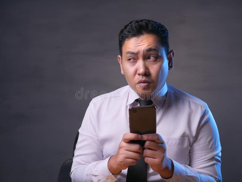 Jonge Mens die terwijl het Babbelen op Smartphone denken royalty-vrije stock foto's