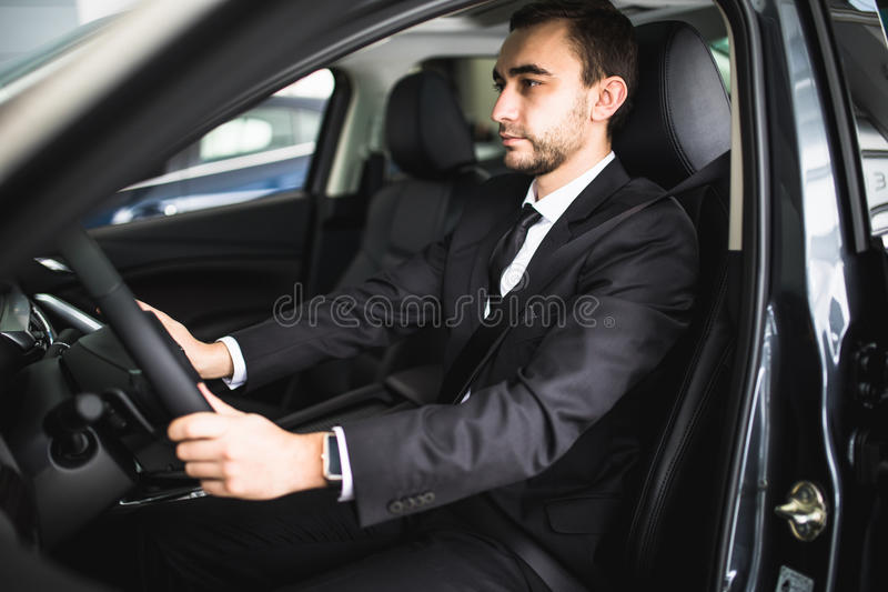 Jonge mens die terwijl het drijven in zijn auto glimlachen stock afbeeldingen