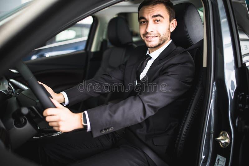 Jonge mens die terwijl het drijven in zijn auto glimlachen stock afbeelding