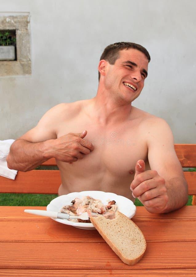 Jonge mens die terwijl het eten glimlachen royalty-vrije stock afbeeldingen