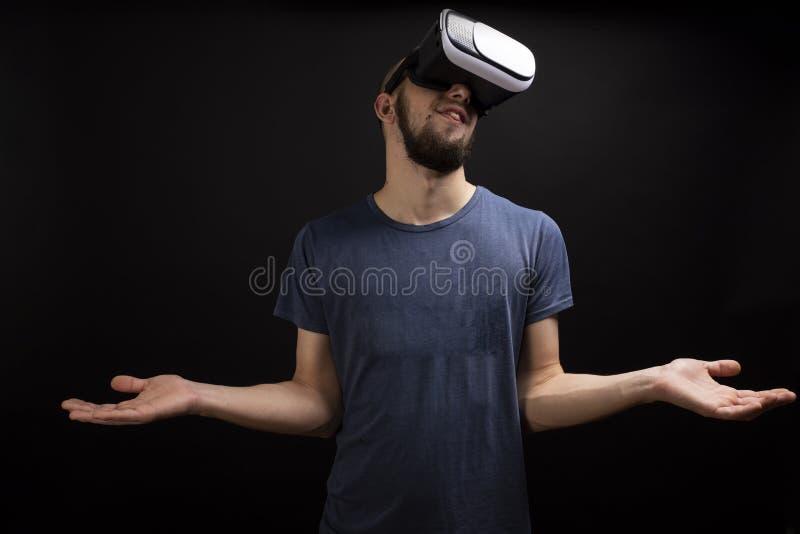 Jonge mens die terwijl het gebruiken van een VR-toestel benieuwd zijn stock fotografie