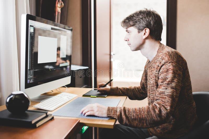 Jonge mens die thuis een computer, een freelance ontwikkelaar of ontwerper het werken gebruiken stock afbeeldingen