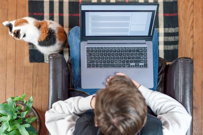 Jonge mens die thuis laptop met behulp van royalty-vrije stock afbeeldingen