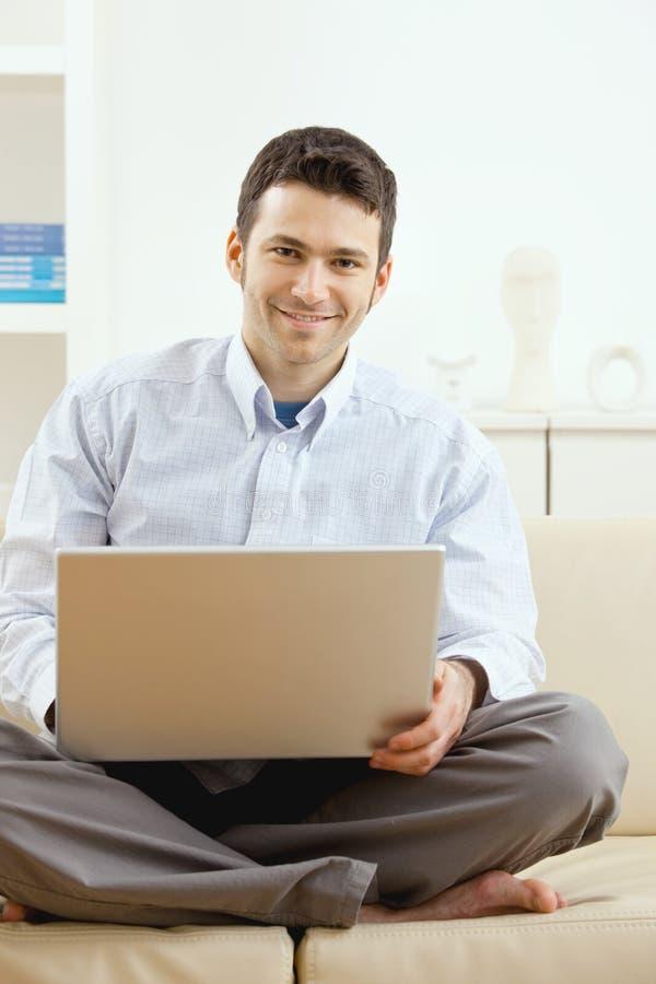 Jonge mens die thuis werkt stock fotografie