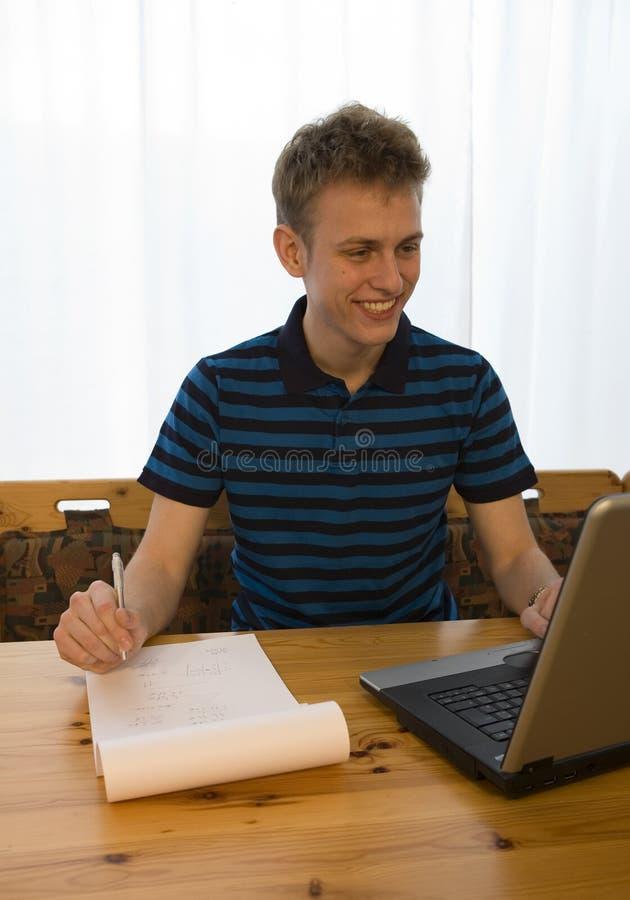 Jonge mens die thuiswerk doet stock foto's