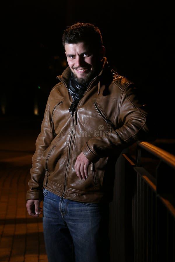 Jonge mens die tijdens een nacht glimlachen royalty-vrije stock afbeeldingen