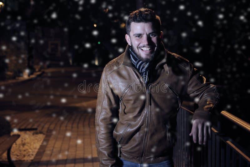 Jonge mens die tijdens een sneeuwnacht glimlachen royalty-vrije stock foto