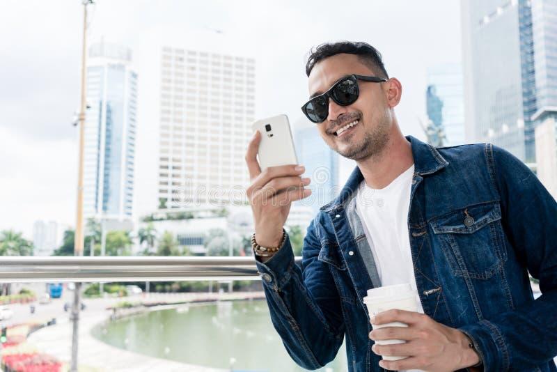 In jonge mens die tijdens online mededeling over zijn smar glimlachen royalty-vrije stock afbeeldingen
