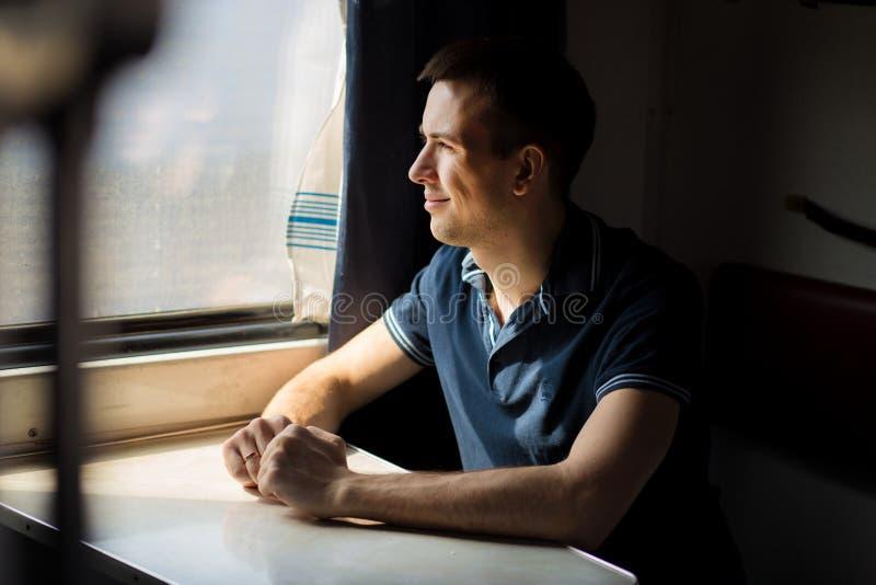 Jonge mens die trein van reis genieten die - zijn auto verlaten thuis, kijkt uit venster, heeft tijd om landschap te bewonderen royalty-vrije stock afbeeldingen