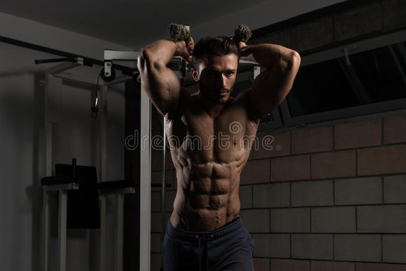 Jonge Mens die Triceps in de Gymnastiek uitoefenen stock afbeelding