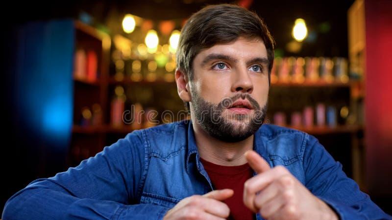Jonge mens die TV-op zitting in bar, wachten voor sportennieuws letten, vrije tijdsactiviteit royalty-vrije stock foto's