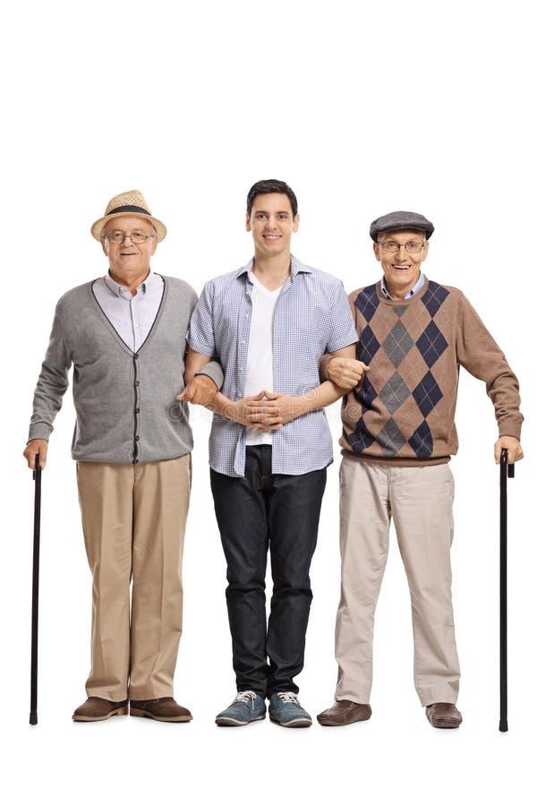 Jonge mens die twee bejaarden met riet helpen royalty-vrije stock foto's