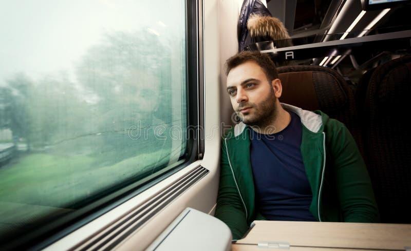 Jonge mens die uit het treinvenster staren royalty-vrije stock foto
