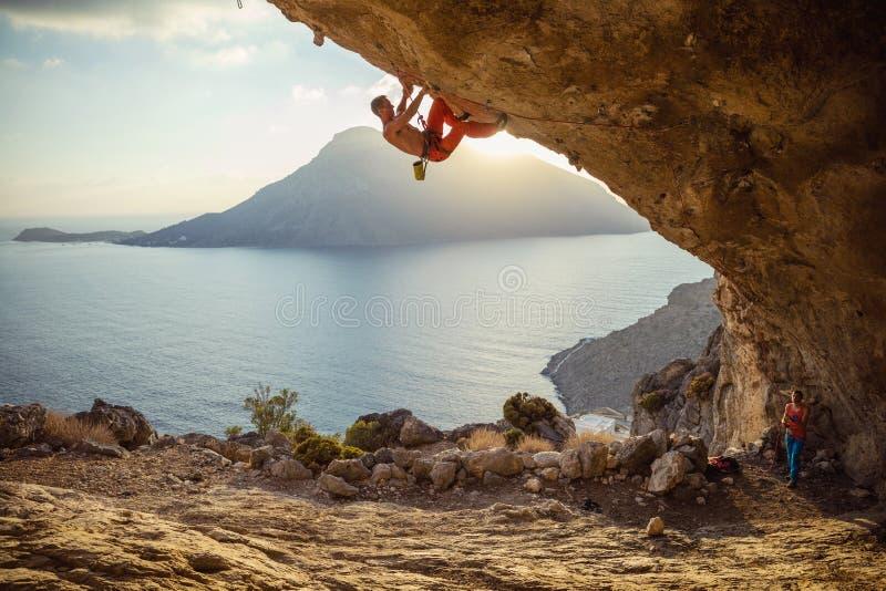 Jonge mens die uitdagingsroute in hol beklimmen bij zonsondergang Zijn partner die hem vastmaken royalty-vrije stock fotografie