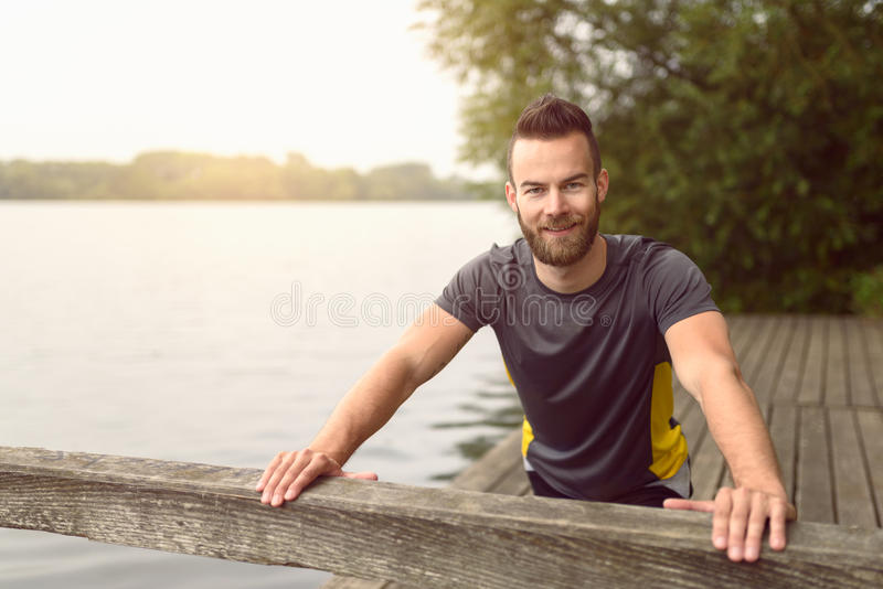Jonge mens die uitrekkende oefeningen op een dek doen stock afbeelding