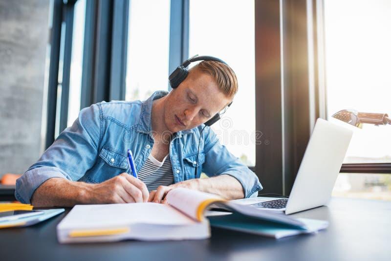 Jonge mens die in universiteitsbibliotheek bestuderen stock foto