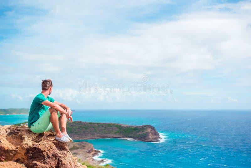 Jonge mens die van adembenemende meningen van Shirley Heights op Antiguaeiland genieten in de Caraïben stock afbeelding