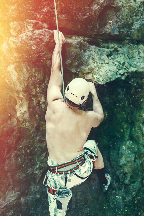 Jonge Mens die in Veiligheidsuitrusting met Uitrusting de Openlucht, Achtermening van de Rotsmuur beklimmen royalty-vrije stock foto's