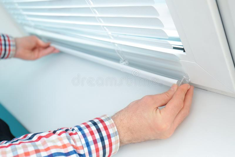 Jonge mens die vensterschaduwen installeren stock fotografie