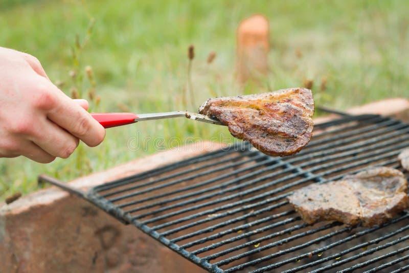 Jonge mens die vlees van de het eigengemaakte tuin grill en geven nemen royalty-vrije stock foto