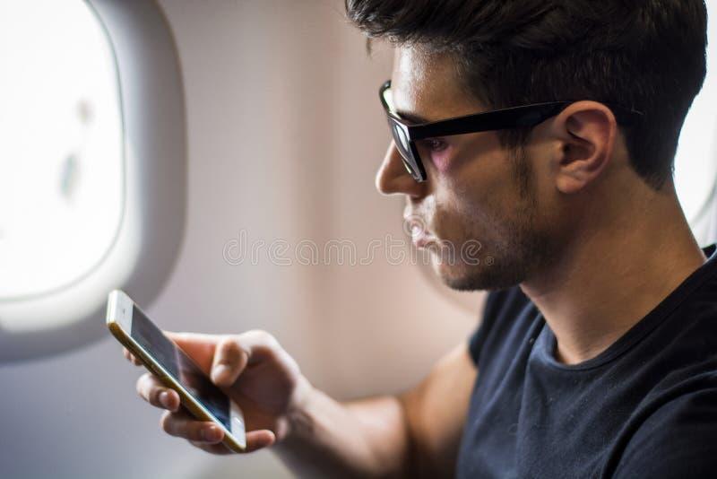 Jonge mens die in vliegtuig aan muziek luisteren royalty-vrije stock foto