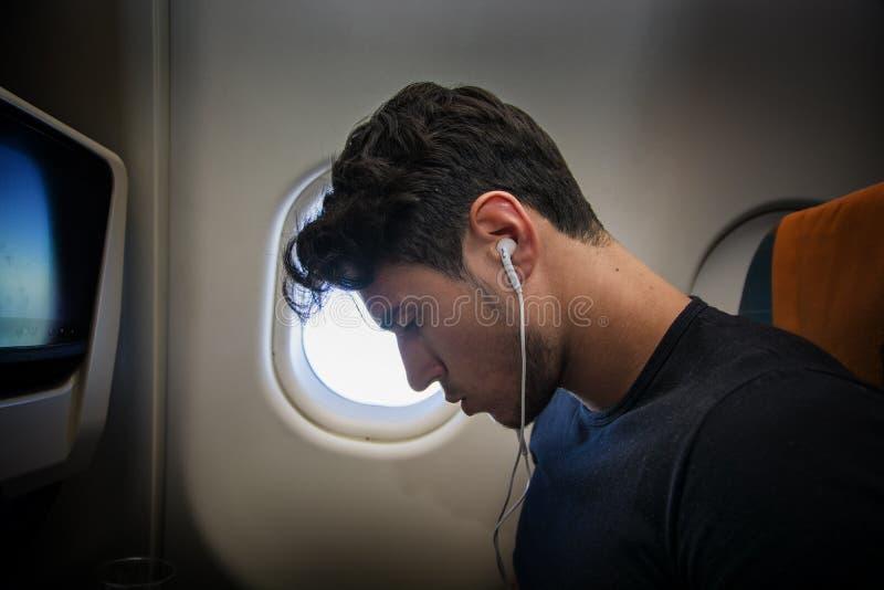 Jonge mens die in vliegtuig aan muziek luisteren royalty-vrije stock fotografie