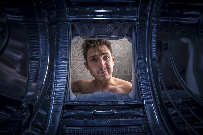 Jonge mens die wasserijweergeven van de binnenkant van gebroken wasmachine doen royalty-vrije stock fotografie