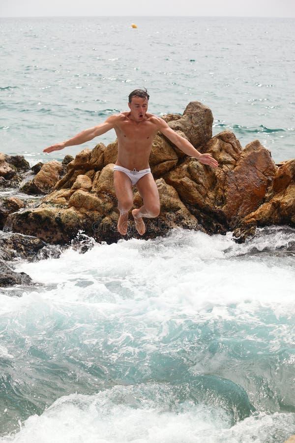 Jonge mens die in water van stapel van rotsen springt stock foto
