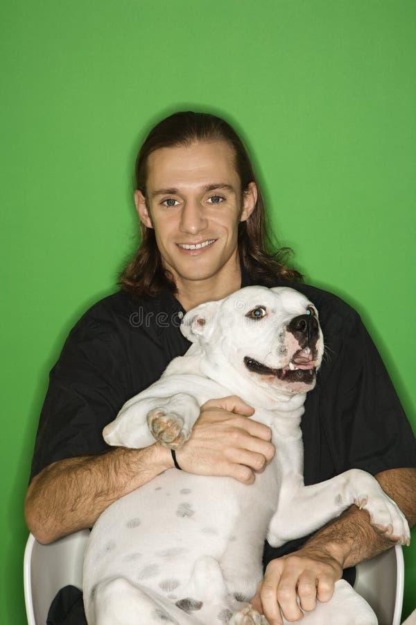 Jonge mens die witte hond op overlapping houdt. royalty-vrije stock foto's