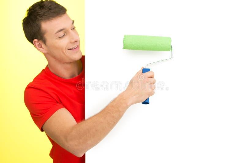 Jonge mens die witte muur schilderen stock foto's