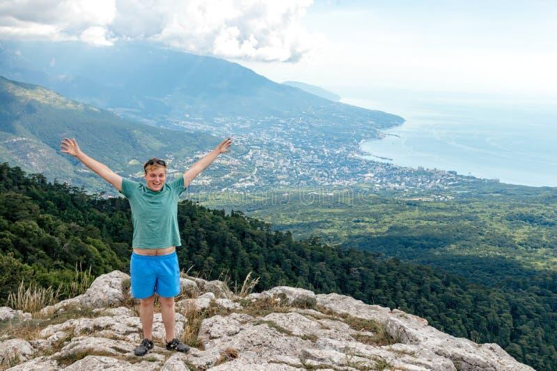 Jonge mens die zich bovenop klip in bergen bevinden en van mening van aard genieten Bergen en Overzees stock foto