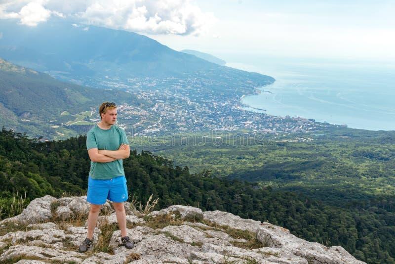 Jonge mens die zich bovenop klip in bergen bevinden en van mening van aard genieten Bergen en Overzees royalty-vrije stock fotografie
