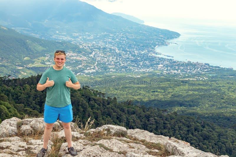 Jonge mens die zich bovenop klip in bergen bevinden en van mening van aard genieten Bergen en Overzees stock afbeelding