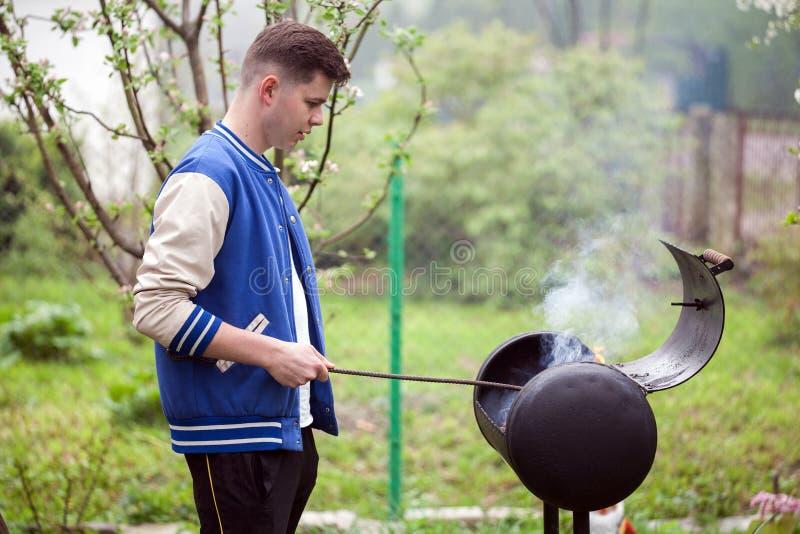 Jonge mens die zich dichtbij barbecuegrill bevinden Het ontsteken van brand in openlucht de zomerpicknick in aard royalty-vrije stock afbeelding