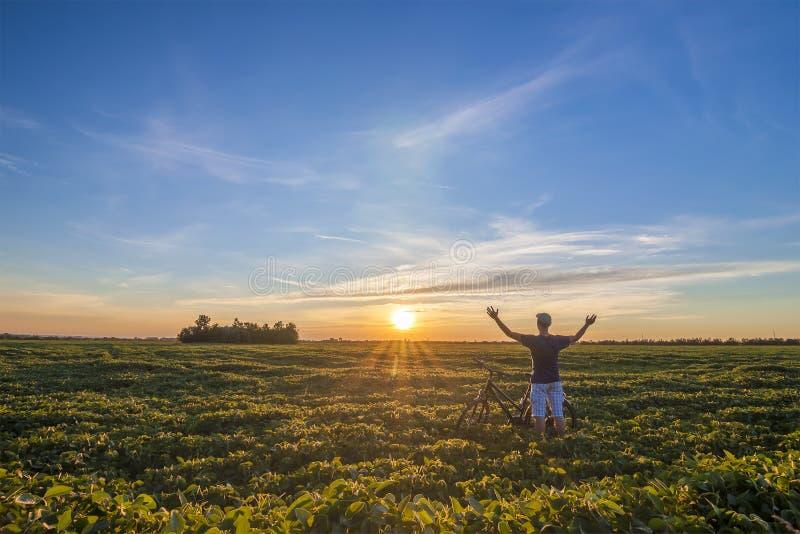 Jonge mens die zich dichtbij fiets in ochtendzonsopgang bevinden met wonderf stock foto