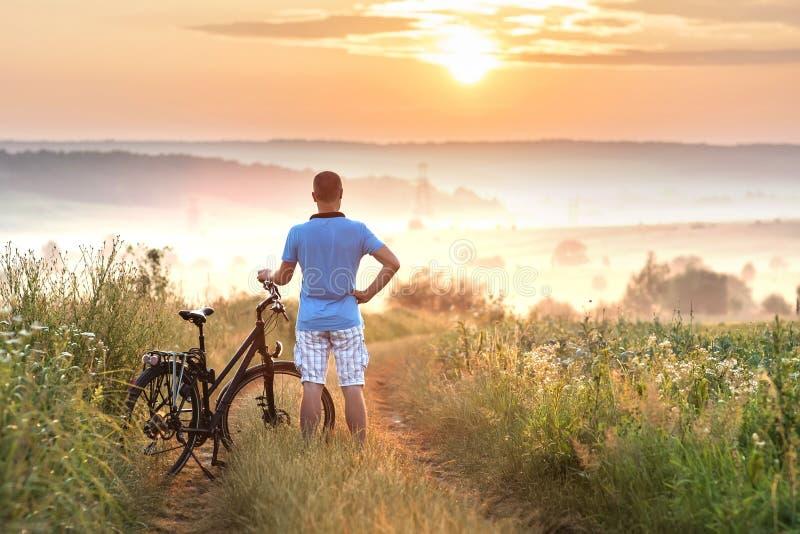 Jonge mens die zich dichtbij fiets in ochtendzonsopgang bevinden met wonderf stock afbeeldingen