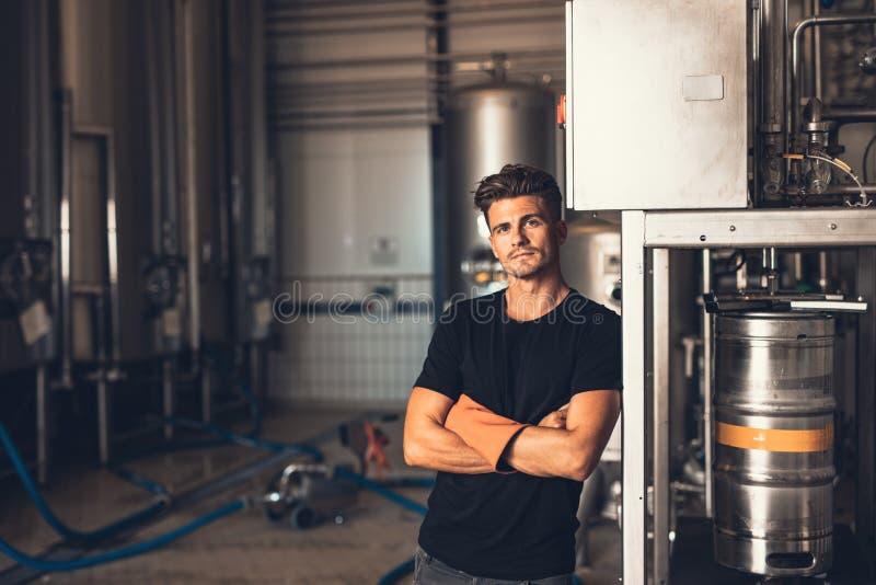 Jonge mens die zich door bier het vullen machine bevinden stock afbeeldingen