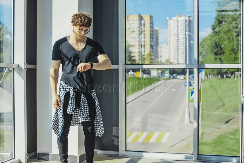 Jonge mens die zich naast grote vensters bevinden en horloges metro post bekijken royalty-vrije stock fotografie