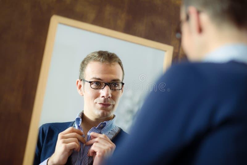 Jonge mens die zich omhoog en spiegel bekijkt kleedt royalty-vrije stock afbeeldingen
