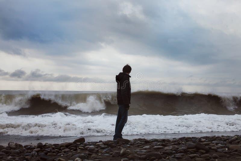 Jonge mens die zich op de overzeese kust bevinden royalty-vrije stock afbeeldingen