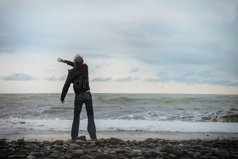 Jonge mens die zich op de overzeese kust bevinden stock fotografie